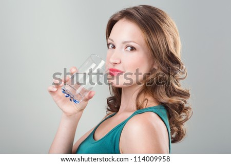 Woman drinking water on grey background. Young woman holding glass of water. Studio shot - stock photo