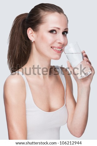 Woman drinking water on white background - stock photo