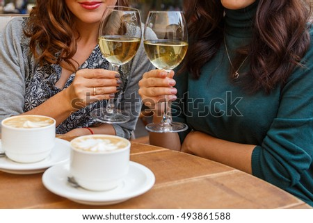 Woman drinking wine and coffee in a cafe