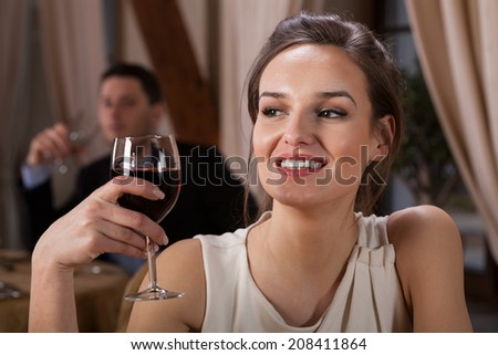 Woman drinking wine in a restaurant, horizontal - stock photo