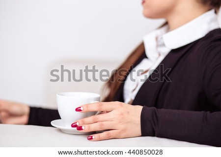 Woman drinks coffee and works on a tablet computer in office lounge zone
