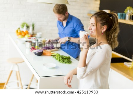 Woman drinks coffee while a man prepares a meal - stock photo