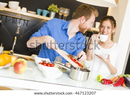 Woman drinks coffee while a man prepares a meal
