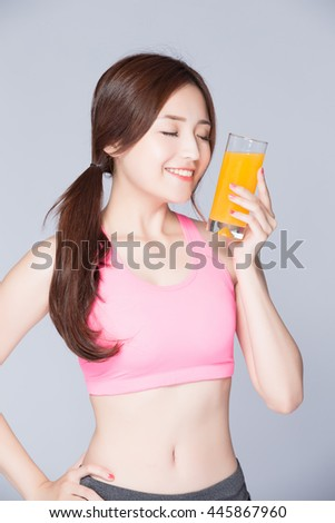 woman drinks orange juice isolated on gray background