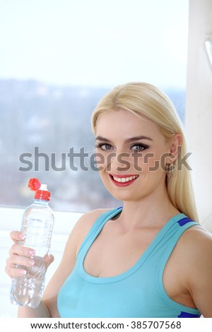 Woman drinks water from a plastic bottle. Concept: sports, fitness at home, shaping, aerobics, healthy lifestyle. - stock photo