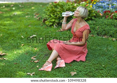 woman drinks water from bottle in the city park - stock photo