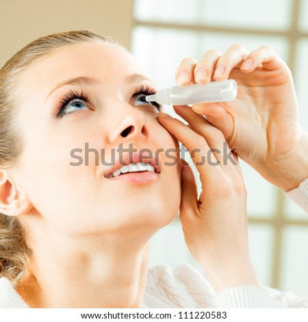 Woman dripping eye with eyes drops