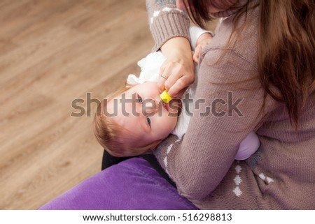 Woman dripping nasal drops to a child