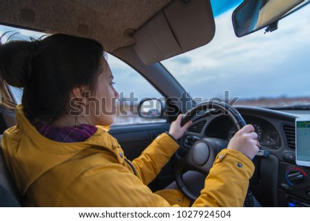 woman drive car in cold winter weather use phone for navigation