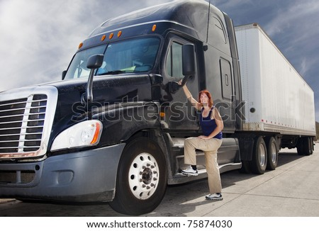 Woman driver at the wheel of her commercial 18-wheeler diesel semi truck. - stock photo