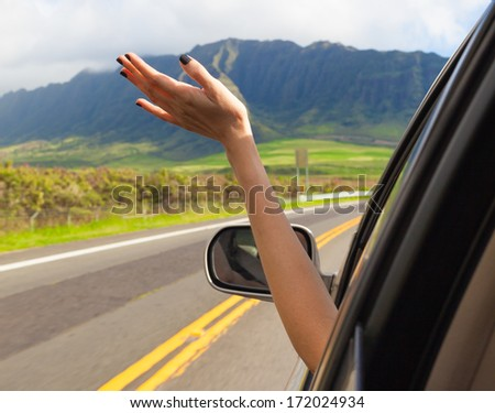 Woman driver feeling the wind through her hands while driving in the country side.(freedom concept) - stock photo