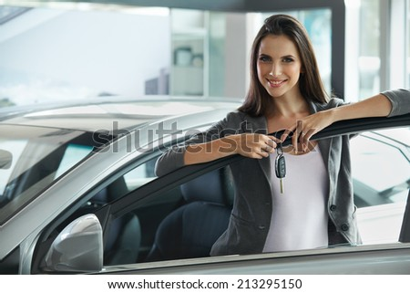 Woman Driver Holding Car Keys. Car Showroom. - stock photo