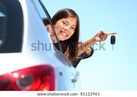 Woman driver holding car keys driving her new car. Beautiful multiracial young woman.