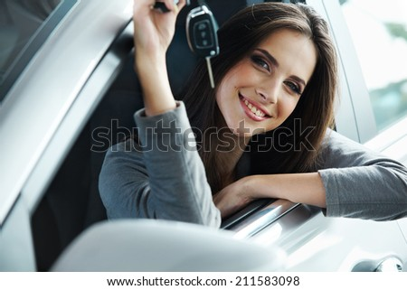 Woman Driver Holding Car Keys siting in Her New Car. - stock photo