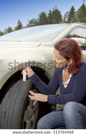 Woman driver measuring tyre profile on car tyre