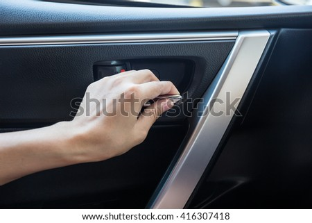 Woman driver pressing button locking and unlocking doors in car.