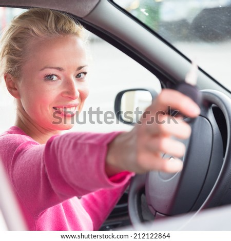 Woman driver showing car keys. Young female driving happy about her new car or drivers license. Caucasian model.