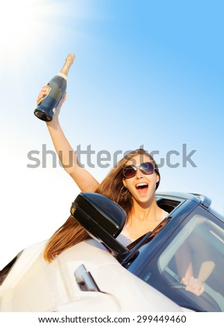 Woman driver showing hand with bottle of champagne. Concept of traveling. Beautiful caucasian young woman. - stock photo