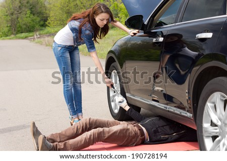 Woman driver watching a mechanic fix her car after breaking down at the side of a rural road handing him a socket spanner as he works under the engine compartment - stock photo