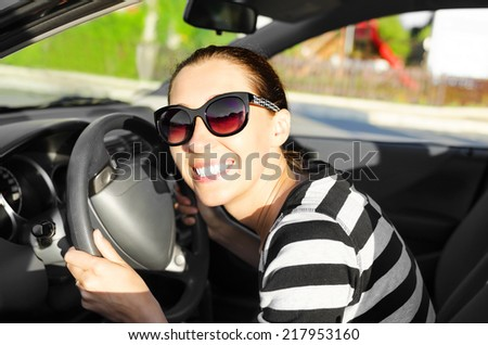 Woman drives a car on the road and smiling