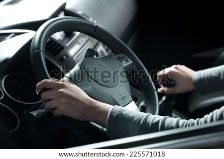 Woman driving a car, hands on steering wheel close-up. - stock photo