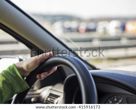Woman driving a car, on a highway.