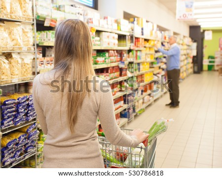 Woman driving a shopping cart in a grocery store