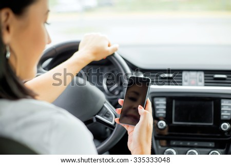 Woman driving and looking at cellphone  - stock photo