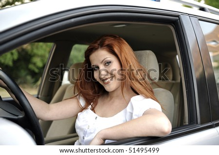 Woman driving car and smiling to camera