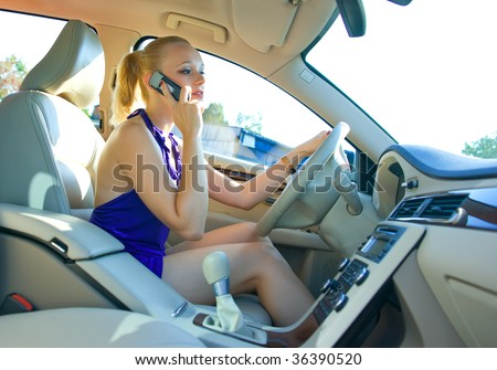 woman driving car and talking on mobile phone - stock photo