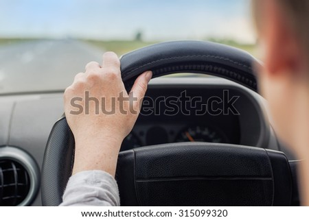 Woman driving car, hand on steering wheel, looking at the road ahead, selective focus on hand with shallow depth of field. - stock photo