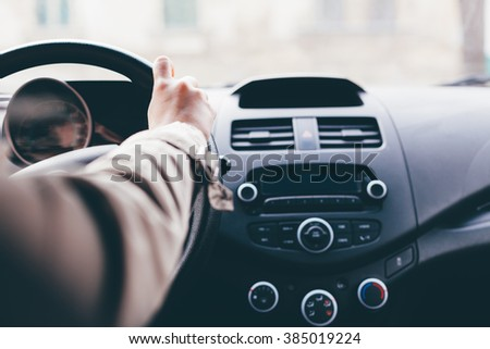 Woman driving car. Hand on the steering wheel. Car interior.
