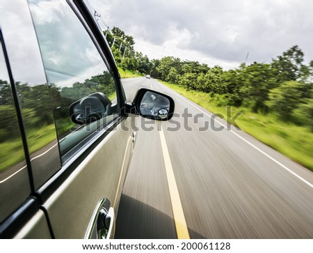 woman driving car on the road with motion blur background