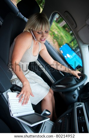 woman driving car while working on mobile phone and laptop - stock photo