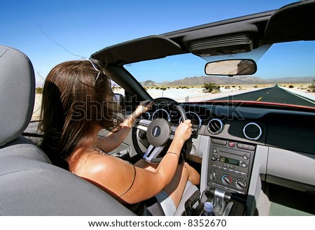 Woman driving convertible on empty road - stock photo