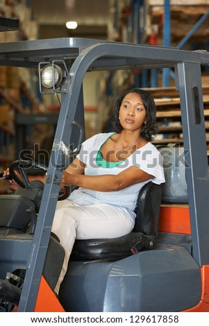 Woman Driving Fork Lift Truck In Warehouse - stock photo