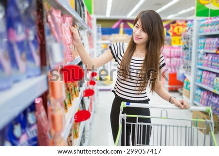 Woman driving shopping cart while grocery shopping in supermarket