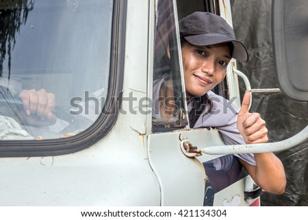 Woman driving trucks. The lorry driver shows gesture thumbs-up. Cheerful woman driving a car with a gesture of success of the open window. - stock photo