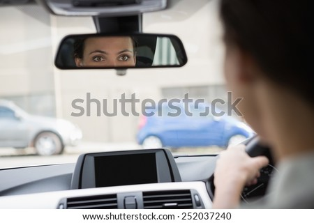Woman driving with her reflection in the mirror in her car - stock photo