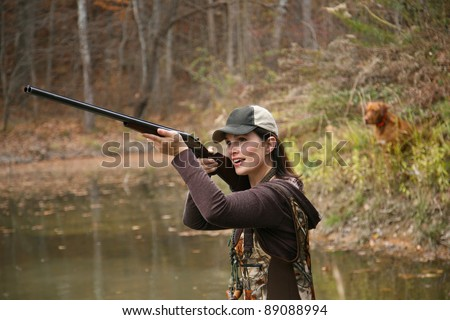 Woman Duck Hunter wearing Cap and Camo Waders Shooting Rifle in Pond with Dog in Background - stock photo