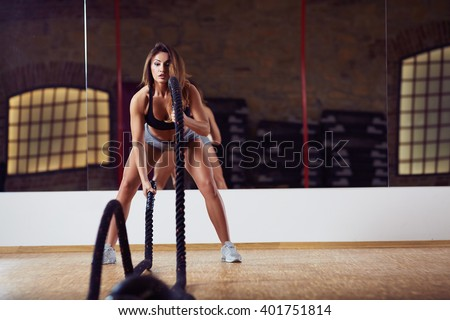 Woman during battle rope workout at gym
