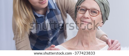 Woman during chemotherapy and girl holding hands on her shoulders, panorama.