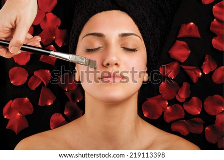 Woman during facial treatment with seaweed mask on bad with roses. - stock photo