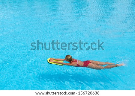 Woman during practice with board from polyfoam for swimming