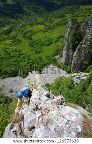 Woman during rock climb high above ground