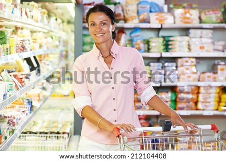 woman during shopping at supermarket with cart trolley - stock photo