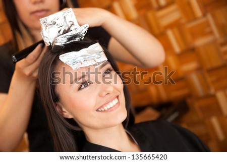 Woman dying her hair at the beauty salon - stock photo
