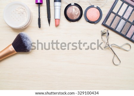 Woman earth tone cosmetics - eyeshadow, brush on, lipstick, eye liner, mascara, powder, brush, eyelash curler. Top view with space for text. - stock photo