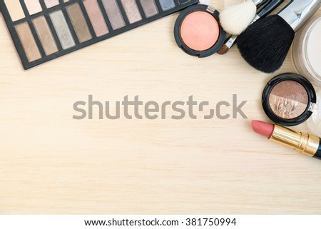 Woman earth tone cosmetics  (makeup) - eyeshadow, brush on, lipstick, powder, brush on wood background. Top view with space for text. - stock photo