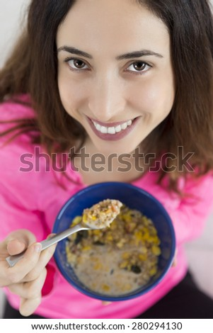 Woman eating a bowl of oatmeal - stock photo